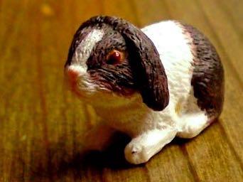 Kaninchen (braun/weiss), kauernd. Kunstharz.